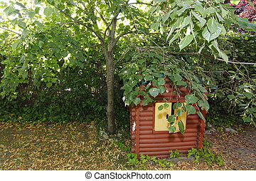 playhouse preserved under a tree full of leaves