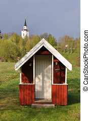 Small red playhouse with a church in the background