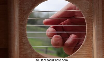 Playing acoustic guitar, slow motion - Playing acoustic...