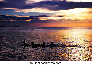 Playing and swimming kids in sea over beautifil sunrise in Thai
