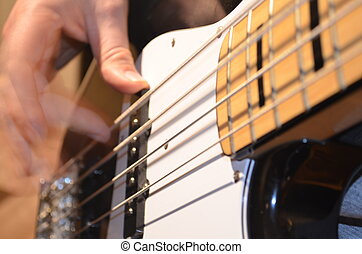 A bassist plucks the strings of an electric bass guitar