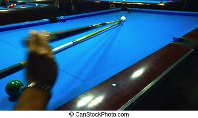 Playing billiard - A shot of a man playing billiard on a blue pool table