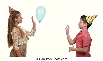 Playing birthday boy with girl of friend being moved balloon
