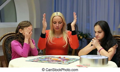 Mother and daughters playing board game