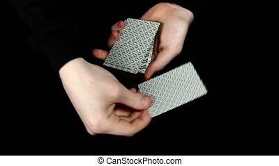 Playing cards being spread, changing the card, on a black surface by magician
