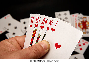 Playing cards in hands on a background of scattered cards.