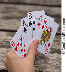 Playing cards in human hands on a wooden background.