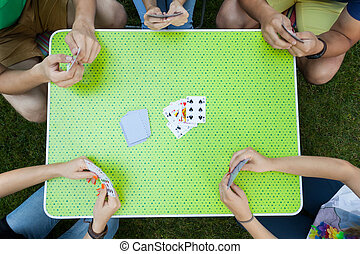 Playing cards on a garden party, horizontal