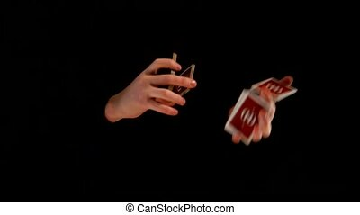 Trick with playing cards making by magician on black background