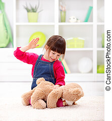 Playing domestic abuse - Angry little girl beating her teddy...