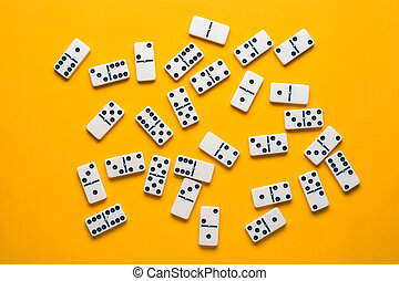 Playing dominoes on a orange table. Domino effect.
