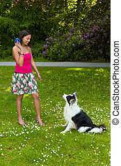 Playing fetch with a border collie dog - Smiling woman...