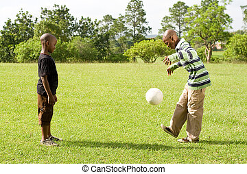 playing football together - two african brothers kicking a...