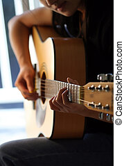 Playing guitar - A woman playing guitar