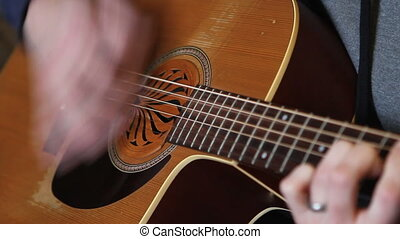 Playing Guitar - Close up of man's hands as he strums out a...