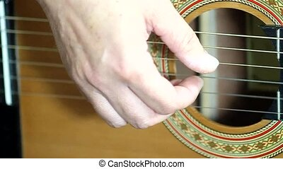 Playing guitar - Close up on a hand playing guitar