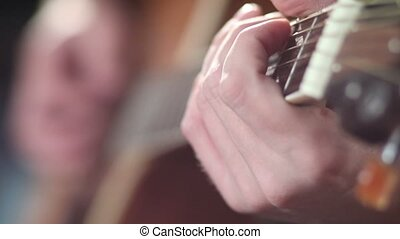 Playing guitar - fingers on fretboard. - Close up male...