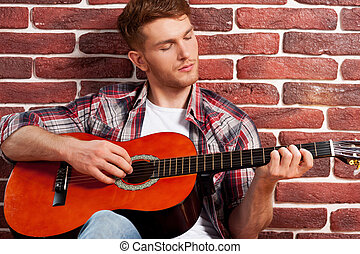 Playing guitar. Handsome young man playing acoustic guitar while leaning at the brick wall