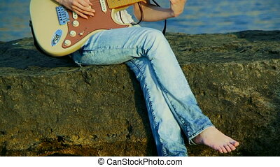Playing guitar - Young beautiful woman playing guitar...