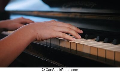 Playing hands of teen girl on the piano