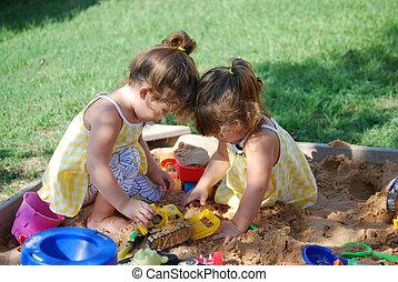 Playing in a sandbox - Twin girls playing in a sandbox