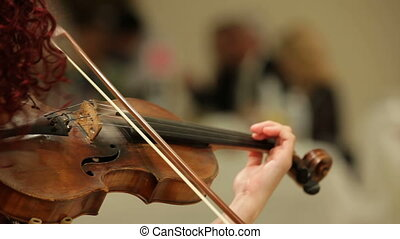 Playing in an orchestra - Young woman playing the violin in...