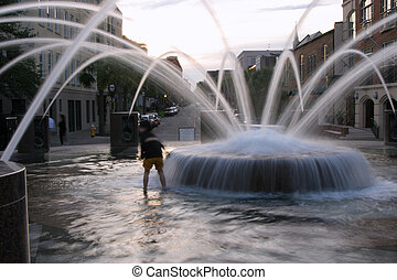 Child playing in a multi-jet fountain, blurred