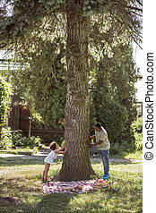 Curly-haired little girl playing with her dad near the tree