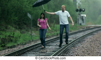 Playing in the rain - Young couple (man and woman),...