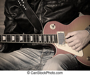 playing in the street in vintage tone - closeup of a guitar...