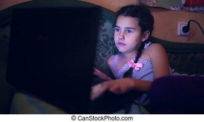 playing laptop teen girl lying on the sofa computer game