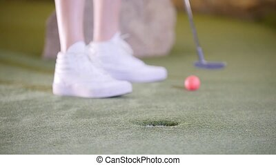 Playing mini golf. A person in white sneakers hitting the...