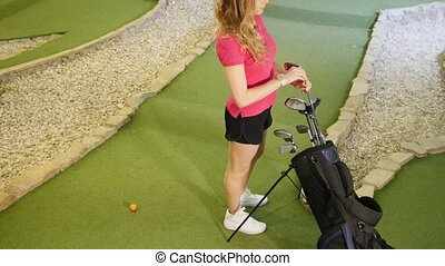 Playing mini golf. A young blonde woman comes to the bag and...