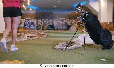 Playing mini golf. A young woman playing mini golf indoors....