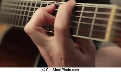 playing on the acoustic guitar. Musical instrument with...
