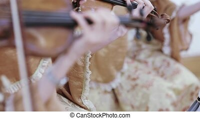 Playing on the cello - A girl in a beautiful dress plays a...