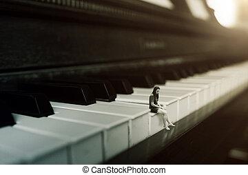 Playing Piano alone - A woman sitting on a key of a piano ...