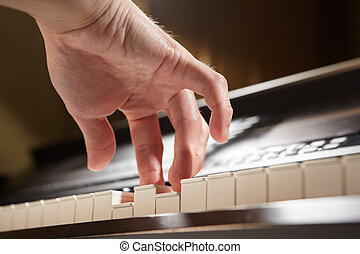 Playing piano from low angle - Hand playing piano taken from...