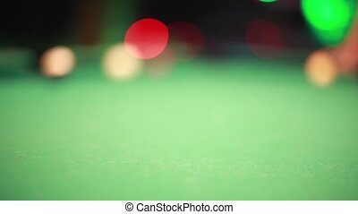 Playing pool billiards in a night bar with bokeh lights on the background.