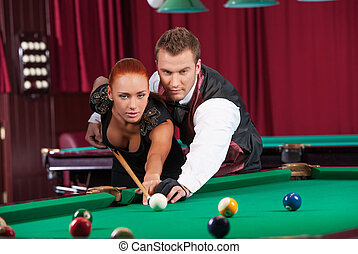 Playing pool. Confident man teaching beautiful young woman to play pool