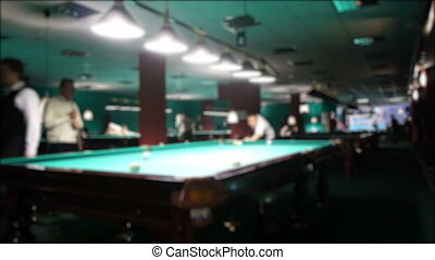 Playing russian billiard in a poolroom, defocused