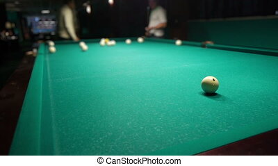 Playing russian billiard in a poolroom, defocused