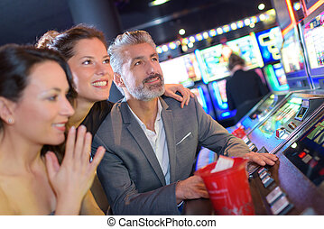 playing slot machines at the casino with girls