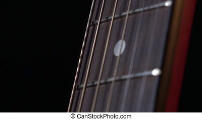 Playing strings of acoustic guitar, down view, first string, on black, close up, slow motion