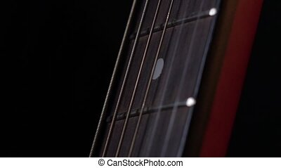 Playing strings of acoustic guitar, down view, third string, on black, close up, slow motion