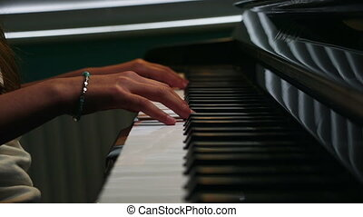 Playing the Piano - Close up of a girls hands playing piano.