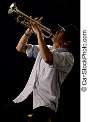 Playing the trumpet - Handsome young man playing a trumpet...