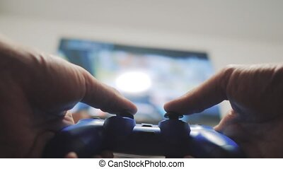 playing video console on tv. Hand hold new joystick...