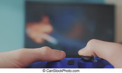 playing video console on tv. Hand hold new joystick online...