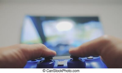 playing video console on tv. Hand hold new joystick playing...
